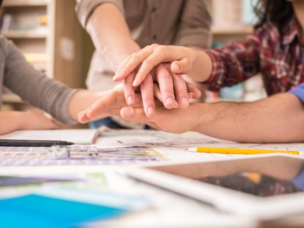 Groupe créatif de designers rassemblant leurs mains.