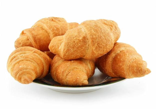 Groupe de croissants sur la soucoupe isolé sur fond blanc