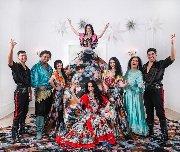 Groupe de danse en costumes folkloriques tsiganes posant sur scène. danse folklorique