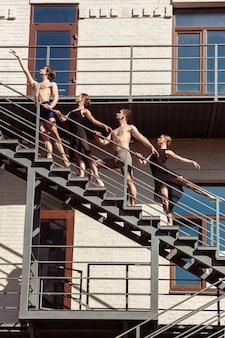 Le groupe de danseurs de ballet modernes effectuant sur les escaliers de la ville