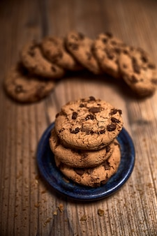 Groupe de délicieux biscuits à côté d'un bol sur une vieille planche de bois