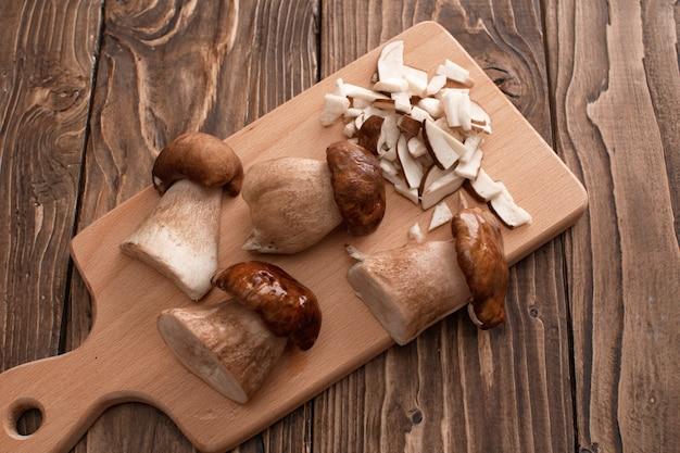 Groupe de délicieux champignons blancs sur une table en bois, partiellement hachés
