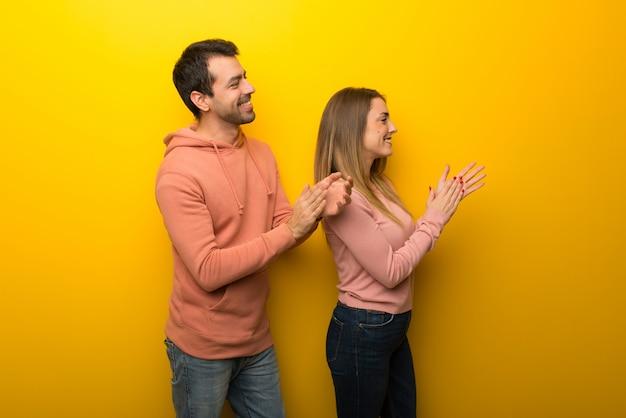 Groupe de deux personnes sur fond jaune applaudissant après la présentation