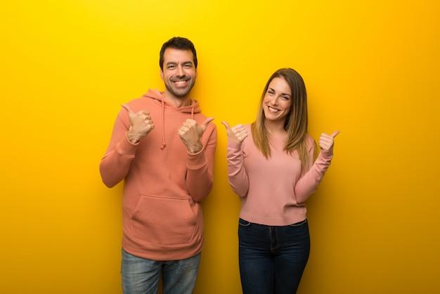Groupe de deux personnes sur fond jaune, donnant un geste du pouce levé