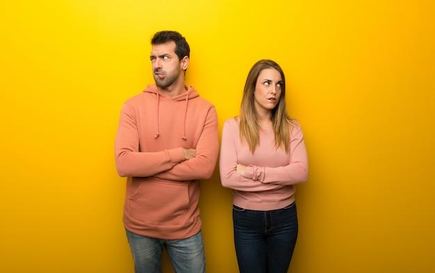 Groupe de deux personnes sur fond jaune avec une expression de visage confuse