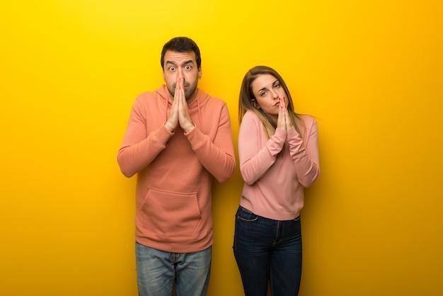 Un groupe de deux personnes sur fond jaune garde la paume de la main.