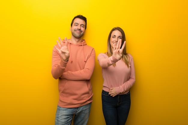 Groupe de deux personnes sur fond jaune heureux et comptant quatre avec les doigts