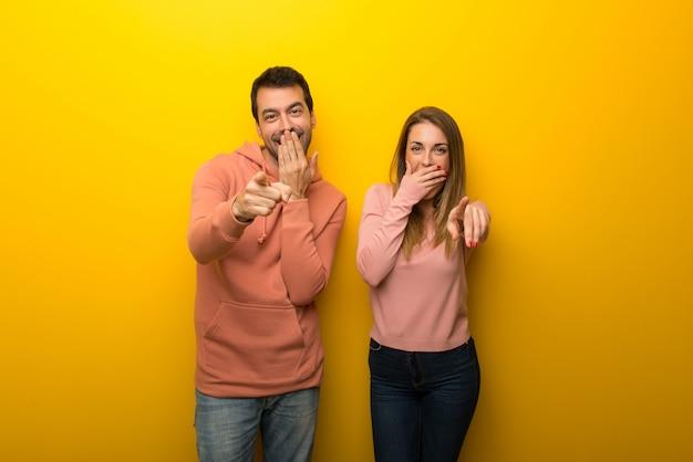 Groupe de deux personnes sur fond jaune, pointant du doigt quelqu'un
