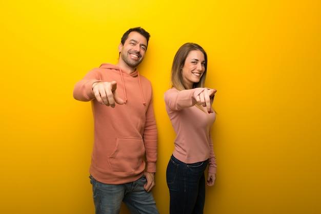 Un groupe de deux personnes sur un fond jaune pointe le doigt vers vous
