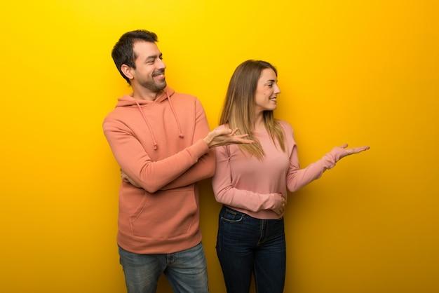 Groupe de deux personnes sur fond jaune présentant une idée
