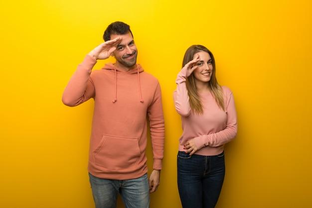 Groupe de deux personnes sur fond jaune, saluant à la main