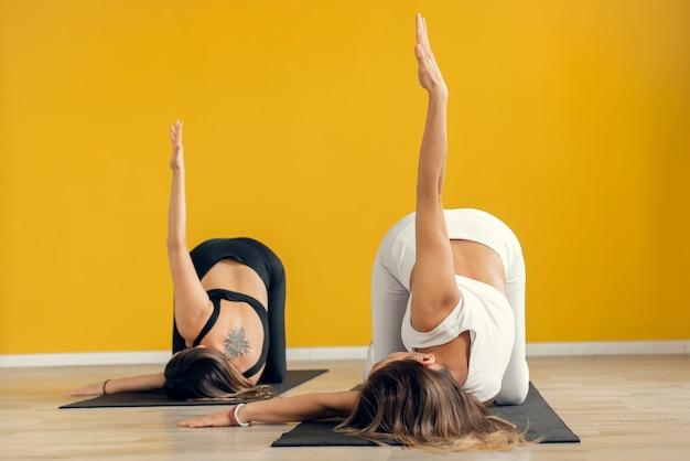Groupe de deux sportifs pratiquant une leçon de yoga, exercice d'étirement pour les enfants, pose de balasana.