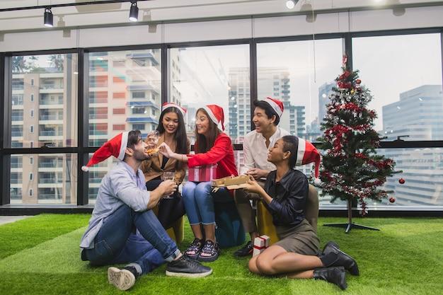 Groupe de dîner multi-générations avec pizza et champagne waring santa hat. groupe d'amis de diverses nationalités ayant une fête de noël avec bonheur