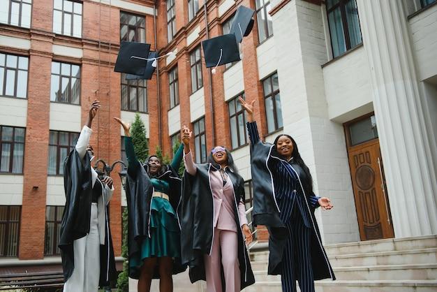 Groupe de diplômés heureux jetant des chapeaux de remise des diplômes en l'air pour célébrer