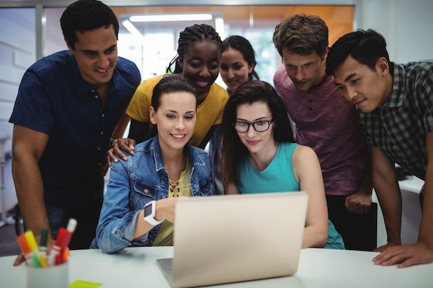 Groupe de dirigeants d'entreprises de discuter sur un ordinateur portable à leur des