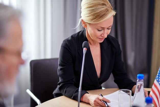 Groupe de dirigeants européens discutant du plan pour l'avenir dans un immeuble de bureaux de démarrage moderne, portant des vêtements formels, assis ensemble à l'aide d'un microphone pour prononcer un discours
