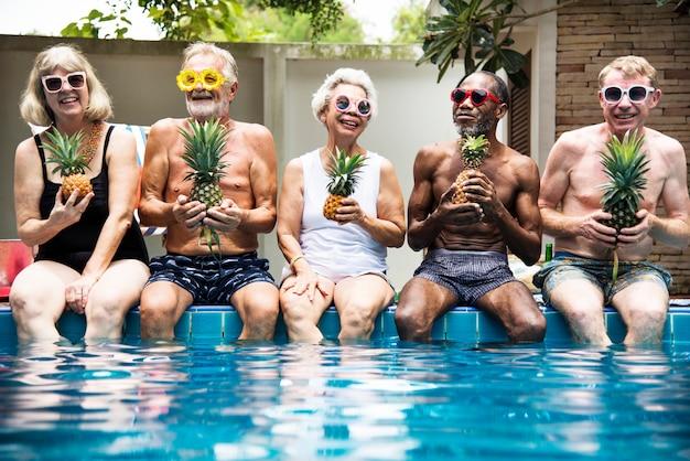 Groupe de divers adultes âgés assis au bord de la piscine, tenant des ananas ensemble