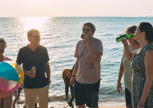 Groupe de divers amis boit à la plage