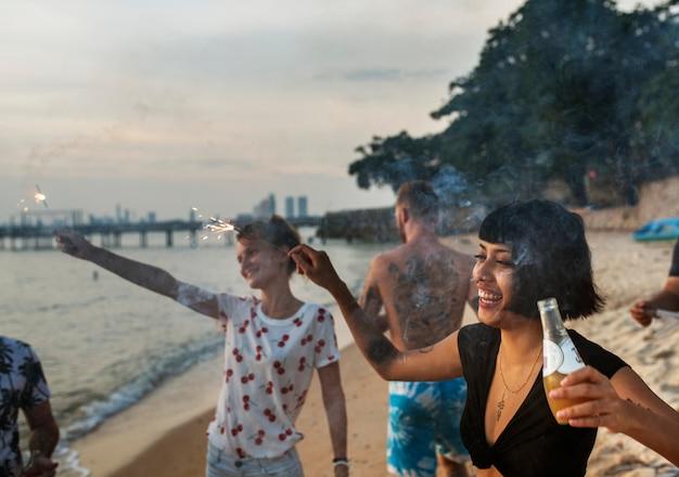 Un groupe diversifié d'amis appréciant des feux de bengale à la plage ensemble