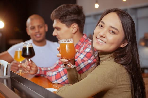 Groupe diversifié d'amis buvant de la bière au pub ensemble