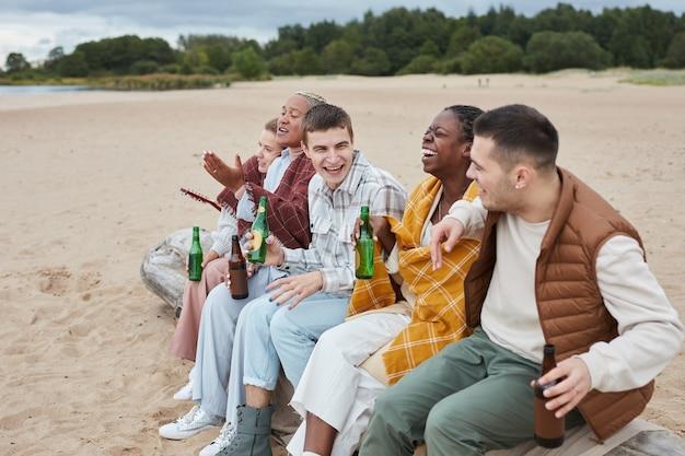 Groupe diversifié d'amis campant sur la plage en automne et s'amusant ensemble à l'extérieur