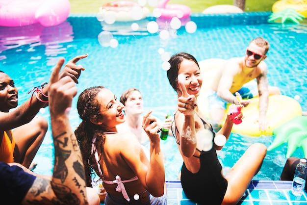 Un groupe diversifié d'amis profitant de l'heure d'été au bord de la piscine