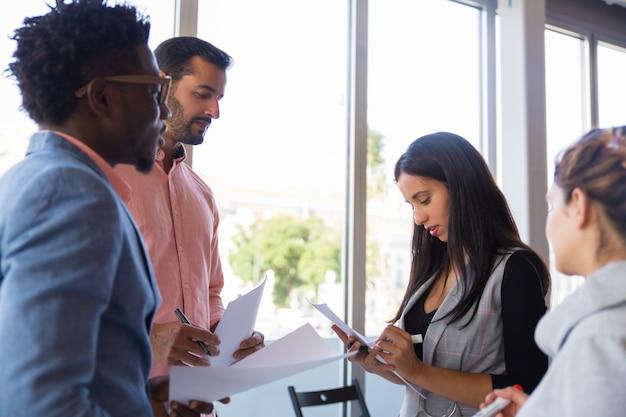 Groupe diversifié de collègues prenant des notes