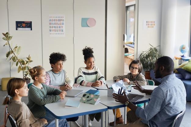Groupe diversifié d'enfants assis à table avec un enseignant dans une salle de classe moderne