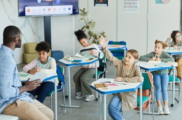Groupe diversifié d'enfants dans une salle de classe avec une fille souriante levant la main, espace de copie