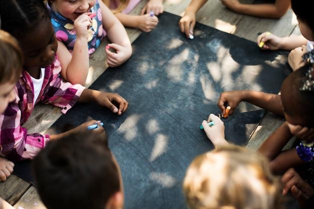 Groupe diversifié d'enfants dessinant sur un tableau noir