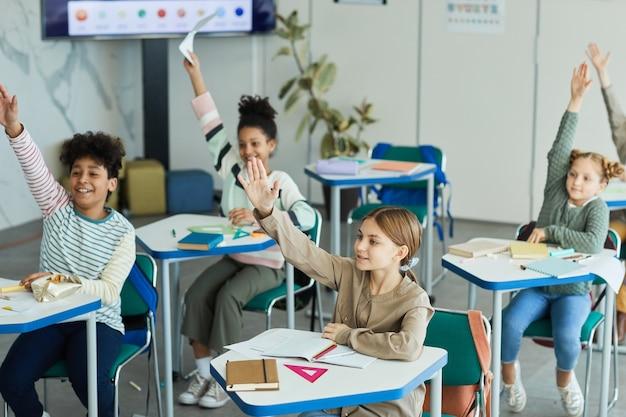 Groupe diversifié d'enfants heureux levant la main dans la salle de classe, espace de copie