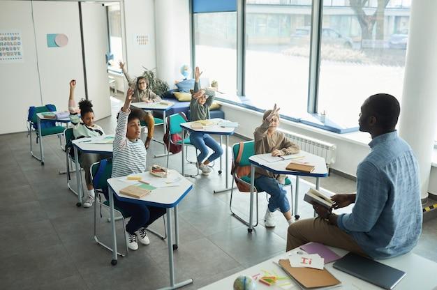 Groupe diversifié d'enfants levant la main dans une salle de classe tout en étant assis à un bureau, espace de copie