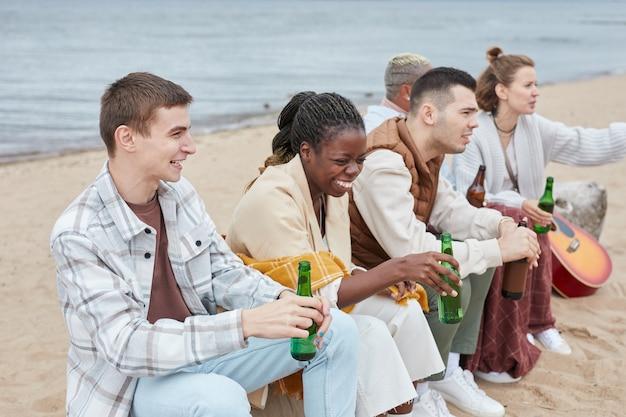 Groupe diversifié de jeunes campant sur la plage en automne et s'amusant ensemble à l'extérieur