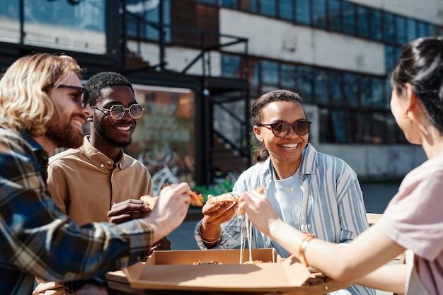 Groupe diversifié de jeunes contemporains appréciant la pizza à l'extérieur, scène éclairée par la lumière du soleil, espace de copie