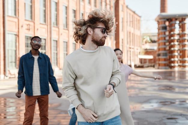Groupe diversifié de jeunes contemporains dansant à l'extérieur dans la rue de la ville, se concentrant sur l'homme insouciant au premier plan