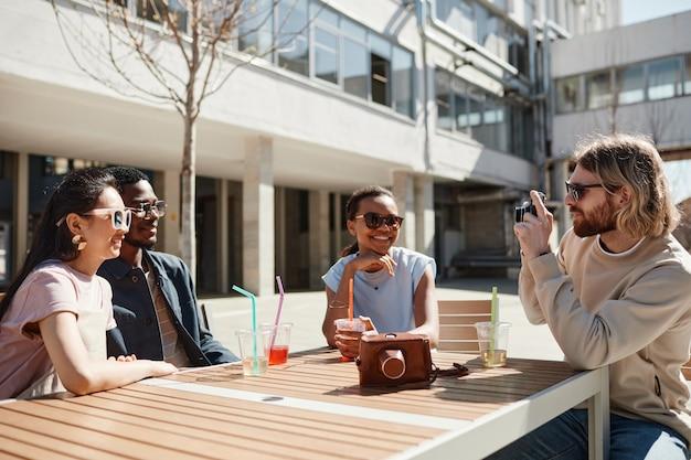Groupe diversifié de jeunes dégustant des cocktails assis à une table de café à l'extérieur éclairé par la lumière du soleil, espace pour copie