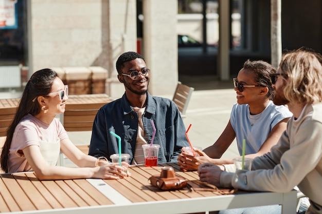 Groupe diversifié de jeunes dégustant des cocktails assis à une table de café à l'extérieur éclairée par la lumière du soleil