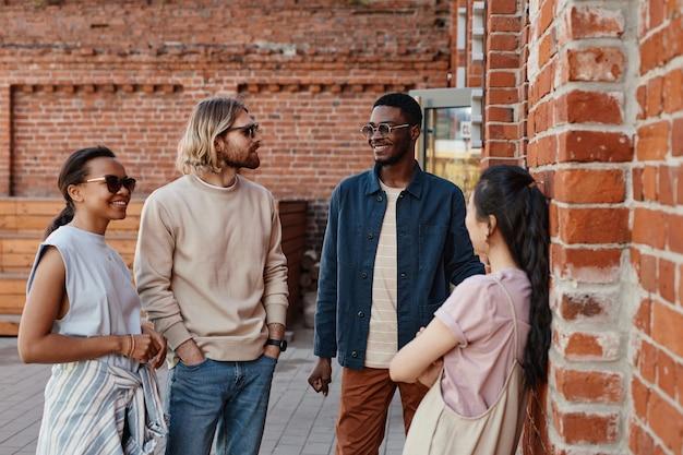 Groupe diversifié de jeunes discutant à l'extérieur tout en se tenant près d'un mur de briques en milieu urbain, espace pour copie