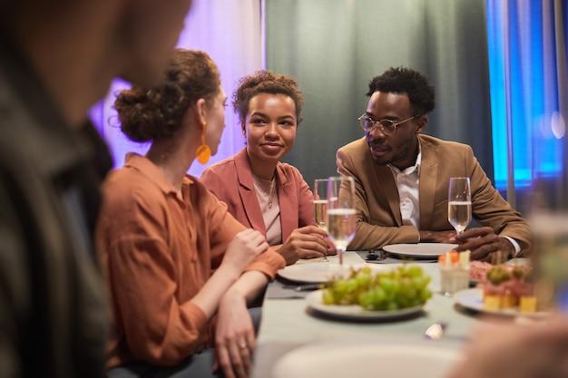 Groupe diversifié de jeunes discutant à table tout en profitant d'un dîner avec des amis