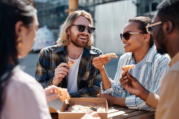Groupe diversifié de jeunes insouciants appréciant la pizza à l'extérieur, scène éclairée par la lumière du soleil, espace de copie