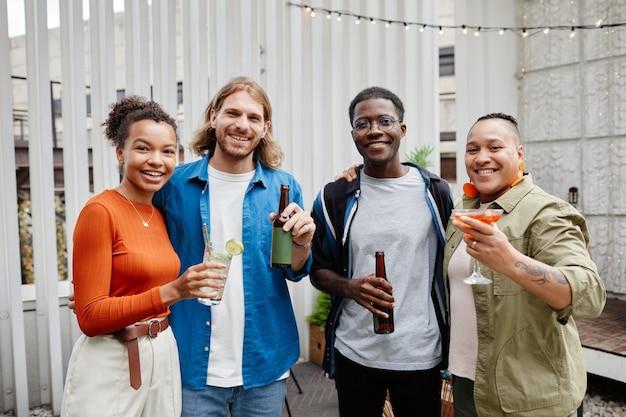 Groupe diversifié de jeunes modernes regardant la caméra tout en s'amusant lors d'une fête sur le toit en plein air