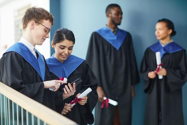 Groupe diversifié de jeunes portant des robes de graduation et utilisant des smartphones à l'intérieur à l'intérieur du collège, espace pour copie