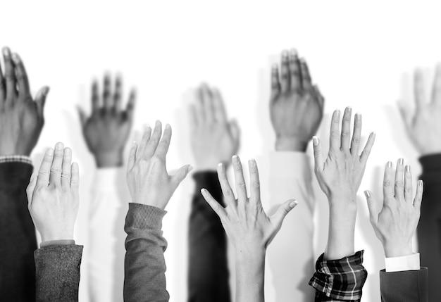 Groupe diversifié de mains levées