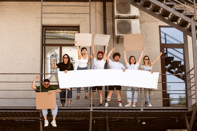Groupe diversifié de personnes protestant avec des signes vierges. protestation contre les droits de l'homme, abus de liberté, problèmes sociaux