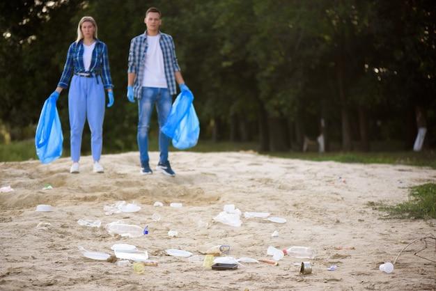 Groupe diversifié de personnes ramassant des ordures dans le parc. service communautaire bénévole.