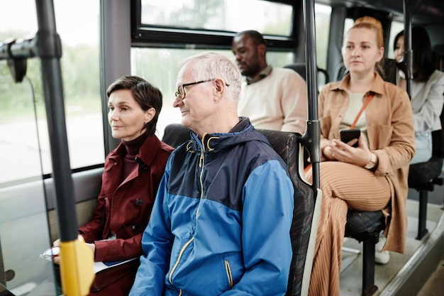 Groupe diversifié de personnes sur des sièges dans des bus publics se déplaçant en ville