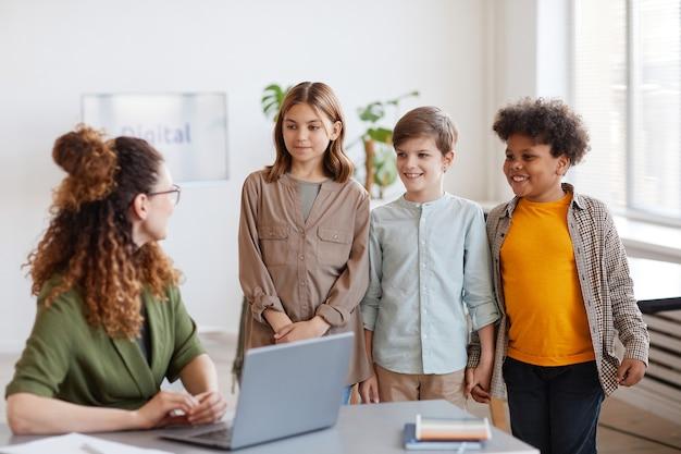 Groupe diversifié de trois écoles parlant à l'enseignant en classe