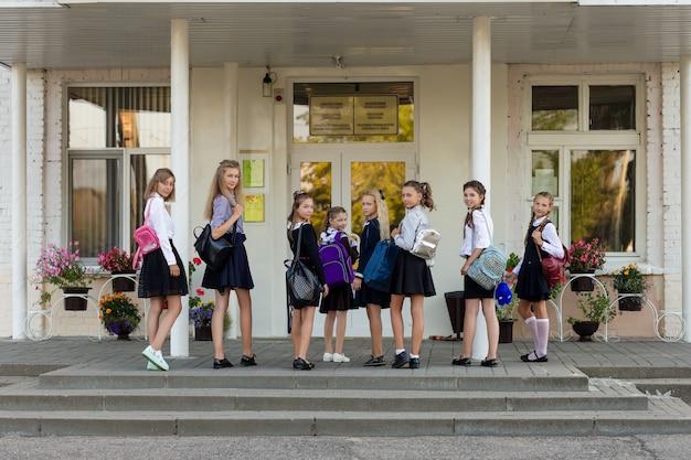Un groupe d'écolières avec des sacs à dos va à l'école