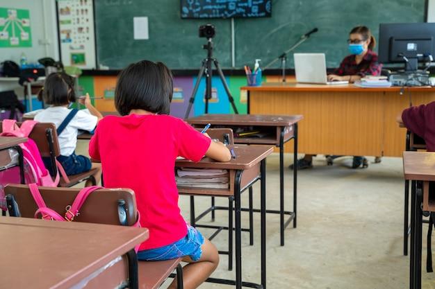 Un groupe d'écoliers portant un masque médical ou un masque chirurgical pour la protéger du virus étudie en classe, protection covid-19 et infection à coronavirus.