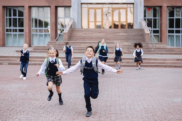 Un groupe d'écoliers en uniforme descend les escaliers à la sortie de l'école.